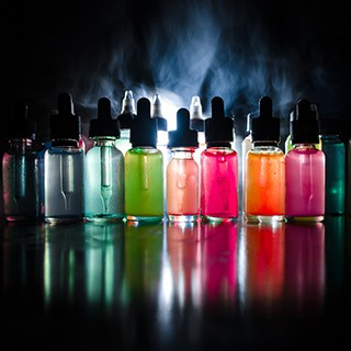 picture of several vials of colored liquid, smoke in background
