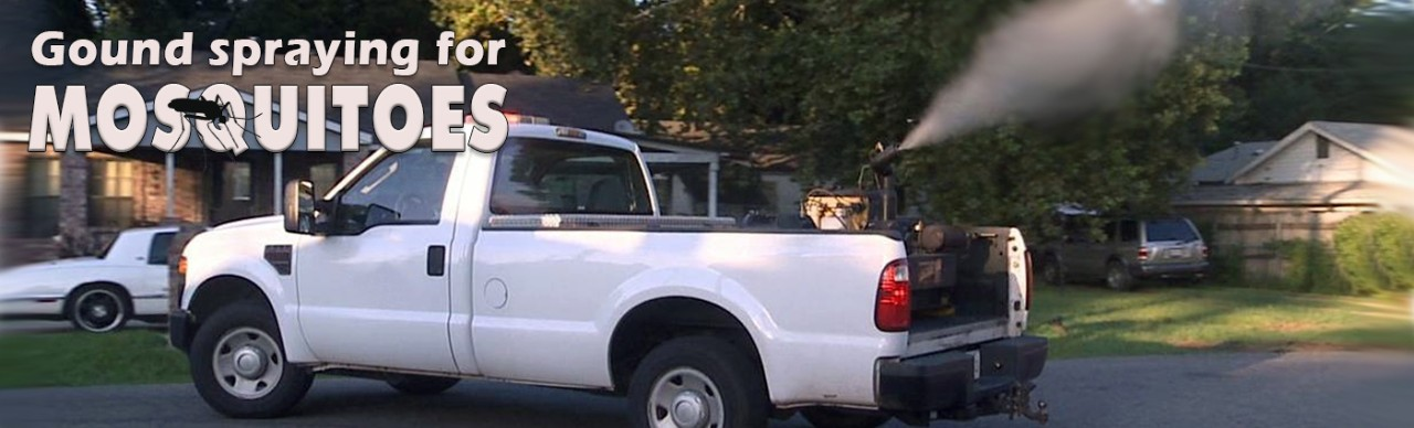 Ground spraying for mosquitoes, white truck with functioning spray device, driving in rural neighborhood