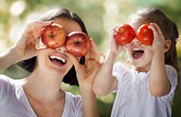 mother, daughter holding fruit over eyes, laughing