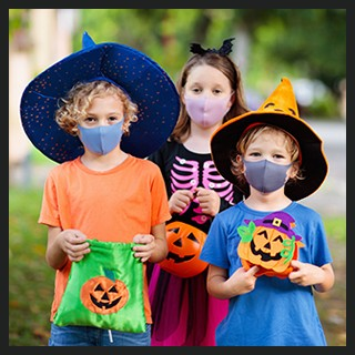 3 children trick-or-treating wearing costumes, protective masks