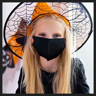 Girl with witch costume, protective mask