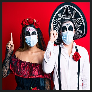 Day of the Dead couple with painted faces wearing costumes, protective masks