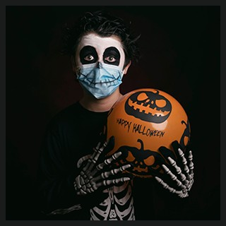boy wearing scary makeup, skeleton costumer, wearing protective mask, holding decorated orange balloon